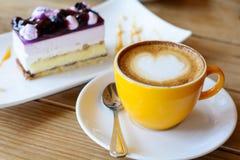 Hete koffie latte kunst en koffieschuim met Bosbessencake op hout Stock Fotografie
