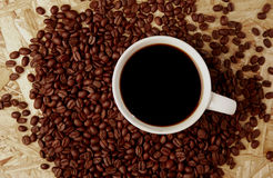 Hete koffie met bonen op houten textuur Stock Afbeelding