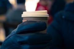 Hete koffie met greep met handhandschoen Stock Foto's