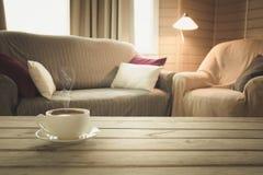 Hete koffie op tafelblad in moderne woonkamer in rustieke stijl Vage abstracte achtergrond voor ontwerp royalty-vrije stock afbeelding