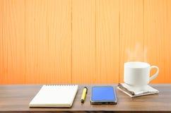 Hete koffie, slimme telefoon, notitieboekje en pen in houten ruimte Stock Fotografie