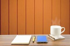 Hete koffie, slimme telefoon, notitieboekje en pen in houten ruimte Royalty-vrije Stock Fotografie