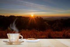 Hete koffiekop en koekje op houten lijstbovenkant op vage weide en berg met zonsopgang en gloedachtergrond royalty-vrije stock foto