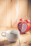 Hete koffiekop en rood klokteken op de klok van 6 o ` Royalty-vrije Stock Fotografie