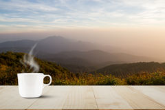 Hete koffiekop met stoom op uitstekende houten lijstbovenkant op vage weide en mistige bergachtergrond tijdens zonsopgang Royalty-vrije Stock Fotografie