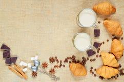Hete latte of mocaccino verfraaide met koffiebonen, croissants, chocolade, kruiden en uitstekende lepels op de bruine doekachterg Stock Afbeelding