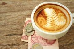 Hete lattekoffie met geld van Thais Bad stock foto