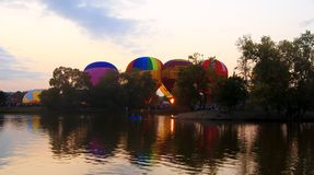 Hete lucht die baloons in de avond hemel dichtbij het meer vliegen Royalty-vrije Stock Afbeelding