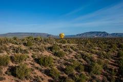 Hete lucht het ballooning over sedona Arizona die ballon en butte tonen stock afbeelding