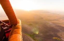 Hete luchtballon busket tijdens zonsopgang die over de vallei vliegen royalty-vrije stock foto's