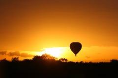 Hete luchtballon die bij zonsopgang over Masai Mara vliegt Stock Foto's