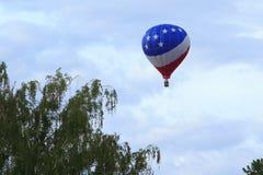 Hete luchtballon die over bomen vliegt Royalty-vrije Stock Afbeeldingen