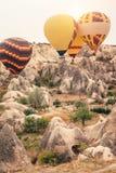 Hete luchtballon die over Cappadocia-berglandschap bij gouden zonsopgang vliegen stock fotografie