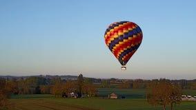 Hete luchtballon die over het landbouwbedrijf vliegen