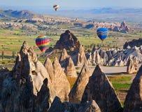 Hete luchtballon die over rotslandschap in Cappadocia, Turkije vliegen Royalty-vrije Stock Foto's