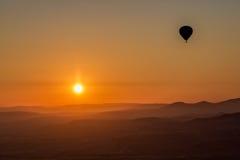 Hete luchtballon die over spectaculaire Cappadocia vliegen stock fotografie