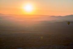 Hete luchtballon die over spectaculaire Cappadocia vliegen stock afbeeldingen