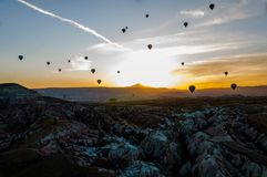 Hete luchtballon die over valleien in Cappadocia Turkije vliegen stock afbeelding