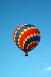 Hete luchtballon die van primaire kleuren in hemel vliegen Stock Afbeeldingen