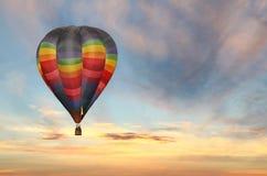 Hete luchtballon in kleurrijke zonsopganghemel Stock Foto
