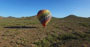 Hete luchtballon in open woestijnvlieg weg stock footage