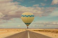 Hete luchtballon over woestijn en weg stock afbeeldingen