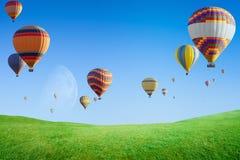Hete luchtballons die in duidelijke blauwe hemel boven groen grasgebied vliegen stock foto's