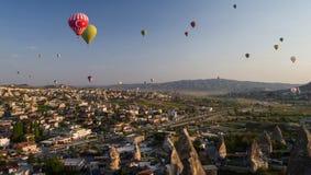 Hete luchtballons die over Goreme bij zonsopgang met zandsteenvormingen vliegen in de voorgrond royalty-vrije stock afbeelding