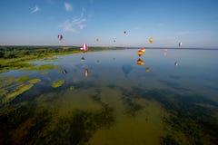 Hete luchtballons die over meer vliegen Stock Foto