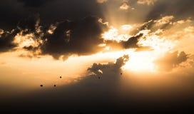Hete luchtballons die in zonsondergang vliegen Stock Afbeeldingen