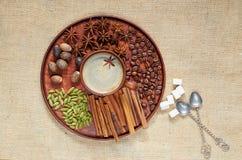 Hete masalathee met diverse kruiden op de bruine plaat: kaneel, notemuskaat, kardemom, anijsplantsterren Aromatische koffie met s stock foto