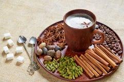 Hete masalathee met diverse kruiden op de bruine plaat: kaneel, notemuskaat, kardemom, anijsplantsterren Aromatische koffie stock afbeeldingen