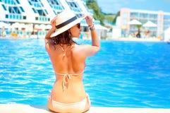 Hete mooie vrouw in hoed en bikini die zich bij pool bevinden stock afbeeldingen
