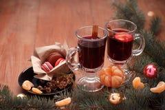 Hete overwogen wijn, mandarijnen en nette takken op een houten lijst Stock Foto's
