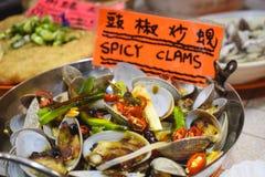 Hete pot met kruidige die tweekleppige schelpdieren op een straatmarkt wordt verkocht in Hong Kong China stock afbeeldingen