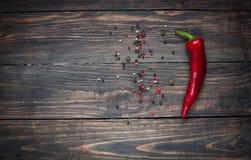 Hete rode Spaanse peperpeper en kleurrijke peperbollen op een houten lijst met plaats voor tekst Royalty-vrije Stock Foto
