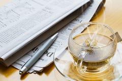 Hete thee, ballpoint en krant Royalty-vrije Stock Afbeelding