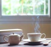 Hete thee en theepot op houten lijst, vensterachtergrond, stock afbeeldingen
