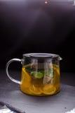 Hete thee met munt en citroen in een glaspot op zwarte achtergrond Royalty-vrije Stock Afbeeldingen