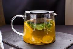 Hete thee met munt en citroen in een glaspot op zwarte achtergrond Stock Foto's