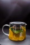 Hete thee met munt en citroen in een glaspot op zwarte achtergrond Stock Afbeelding