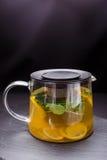 Hete thee met munt en citroen in een glaspot op zwarte achtergrond Stock Fotografie