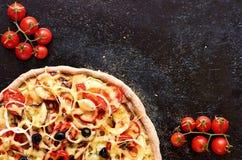 Hete vegetarische pizza met tomaten, groene paprika, ui, zwarte olijven, kaas, kruiden op de donkere zwarte achtergrond van het b Royalty-vrije Stock Foto's