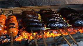 Hete vleespennen met groenten bij de grill De aubergines, de tomaten en de groene paprika's zijn gebraden op steenkolen stock footage