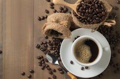 Hete zwarte koffie op kop en geroosterde koffiebonen in houten lepel o Royalty-vrije Stock Foto