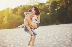 Heterosexual Couple on the beach having fun, in a backlit Royalty Free Stock Images