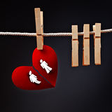 Heterosexual couple breaking apart, conceptual love image. Of paper heart ripped in two, hanging on rope with clothes pin Royalty Free Stock Image