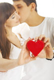 Heterosexual couple with a heart. Kissing heterosexual couple with a heart on white background Royalty Free Stock Photo