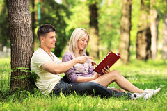 Heterosexual couple seated on a grass and reading a novel in a p. Heterosexual couple seated on a green grass and reading a novel in a park Royalty Free Stock Images
