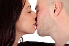 Heterosexual loving couple. Young Caucasian  heterosexual loving couple kissing each other,  Studio, white background Royalty Free Stock Photo